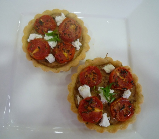 Tartlets filled with aubergine pure, roasted tomato & goats cheese.