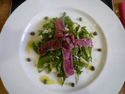 Beef carpaccio on a salad of rocket, capers and parmesan.